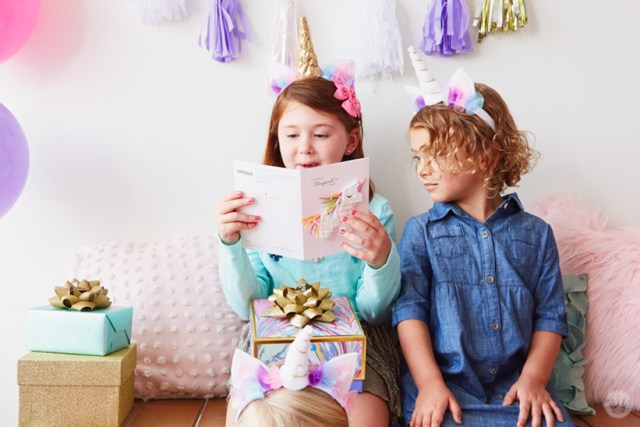 Two girls reading a Signature unicorn birthday card
