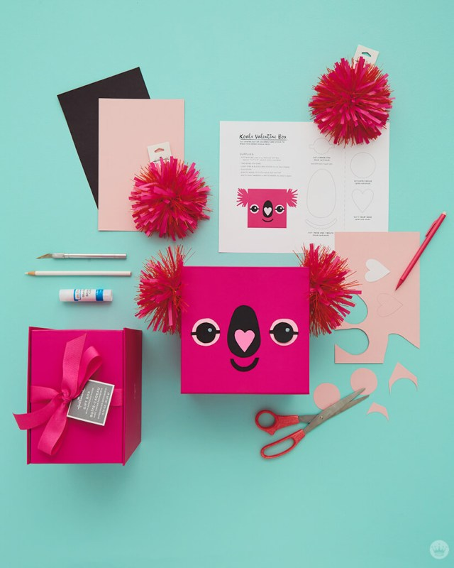 Instructions and supplies (paper, ribbon, craft knife, pencil, glue stick, gift box, pen, scissors) for Pink Koala valentine mailbox