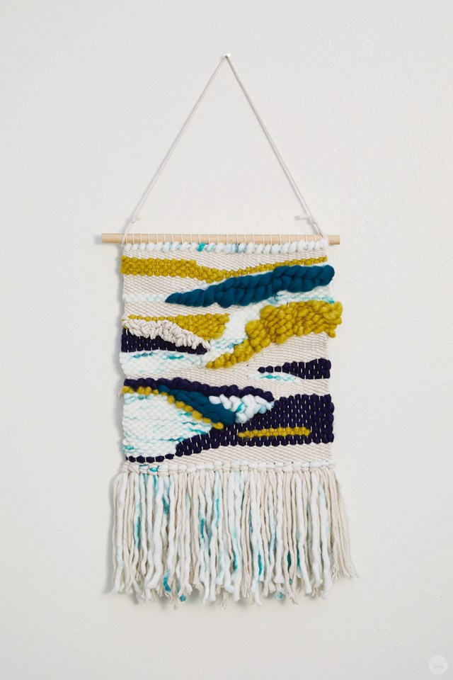 Weaving workshop: finished piece of fiber art in simple palette with tassels and roving