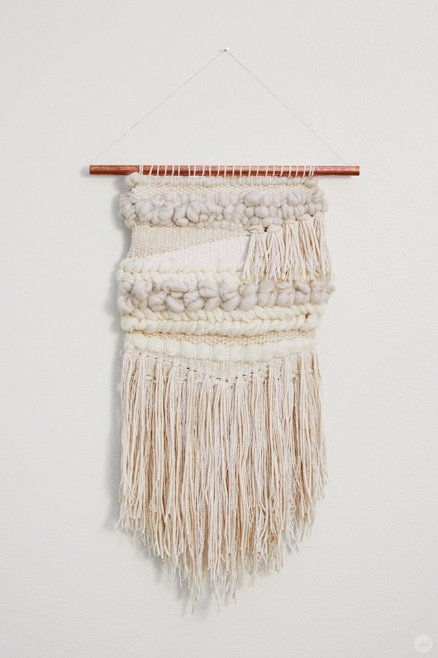 Weaving workshop: finished piece of fiber art in monochromatic palette with tassels and roving