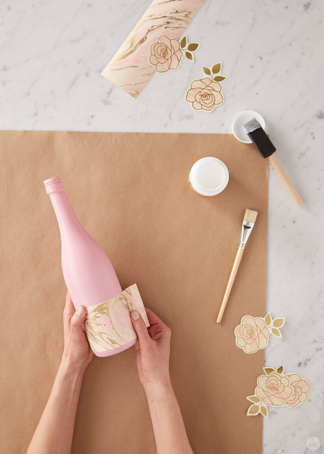 Upcycled wine bottles: Gluing wrapping paper designs to wine bottles   thinkmakeshareblog.com