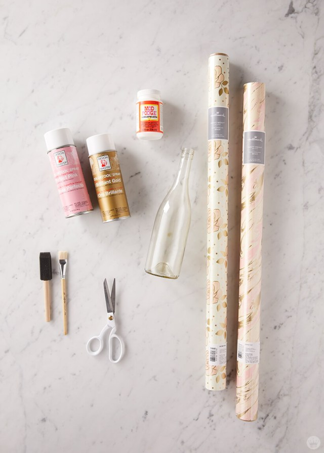 Upcycled wine bottle supplies: spray paint, decoupage glue, wrapping paper, bottle, brushes, scissors | thinkmakeshareblog.com