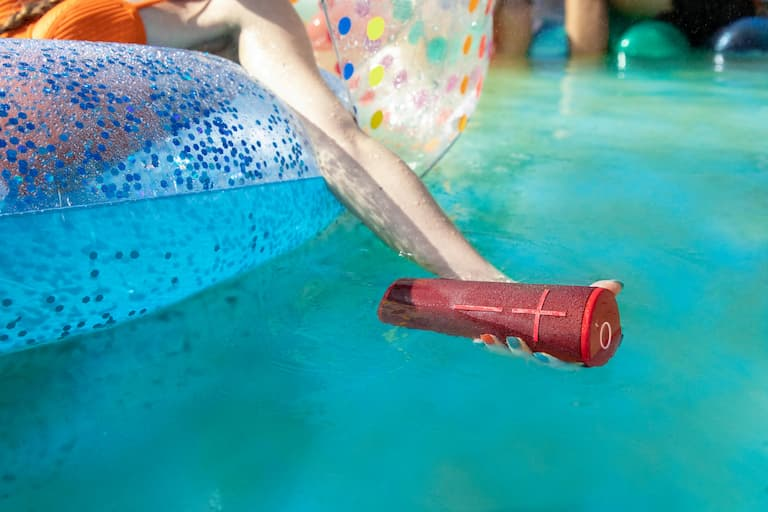 woman lounging in water holding ultimate ears speaker