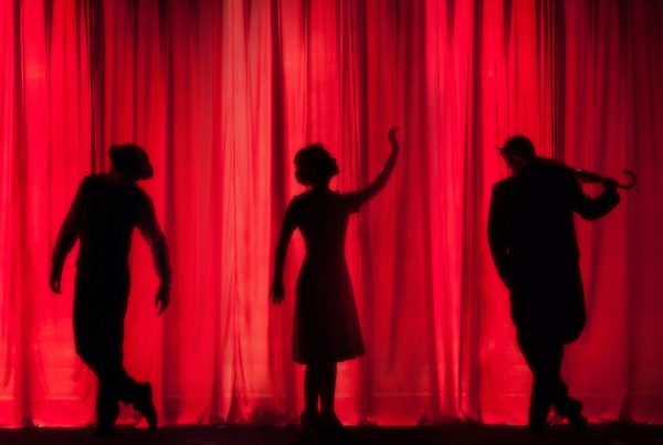 Silhouette of 3 actors on stage in front of a red curtain