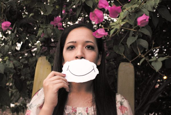 Woman who looks sad with the picture of a smile in front of her mouth