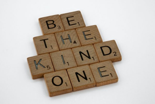 Scrabble pieces spelling out 'be the kind one'