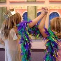 Two children with longer blond hair wearing crowns and feather boas, playing dress up in front of a pink castle set