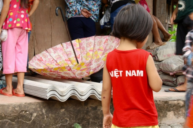 Image of a young girl taking in the chaos of the crowd as RAKLife handed out clothing in Xom Pung Village Vietnam.
