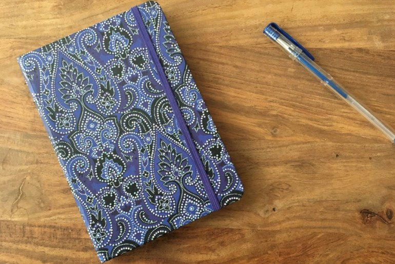 Image of intricately designed blue Nectar List journal and pen on wood table.