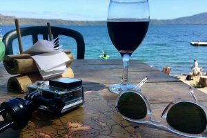 Image of the view of Laguna de Apoyo from San Simian Eco-Lodge including a glass of wine, GoPro, and sunglasses.