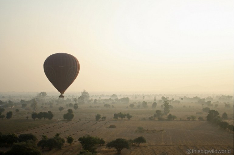 Image of lone hot air balloon floating over the temples of Bagan on a foggy morning.