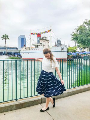 Girl with white shirt and blue skirt stands in front of a lake. In the background is a ship.