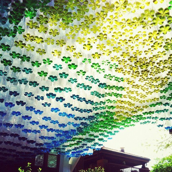 Recycled Plastic Bottles Partially Filled with Colored Water Used to Create a Parking Canopy street art recycling architecture
