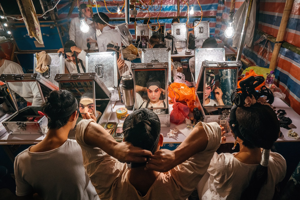 Performances of Chinese opera are usually held in a mat-shed at the Pak Tai Temple in Taipa village. In this small temporary make-up room built solely with bamboo and iconic red-blue-white plastic bags, over 10 performers are preparing for the show.