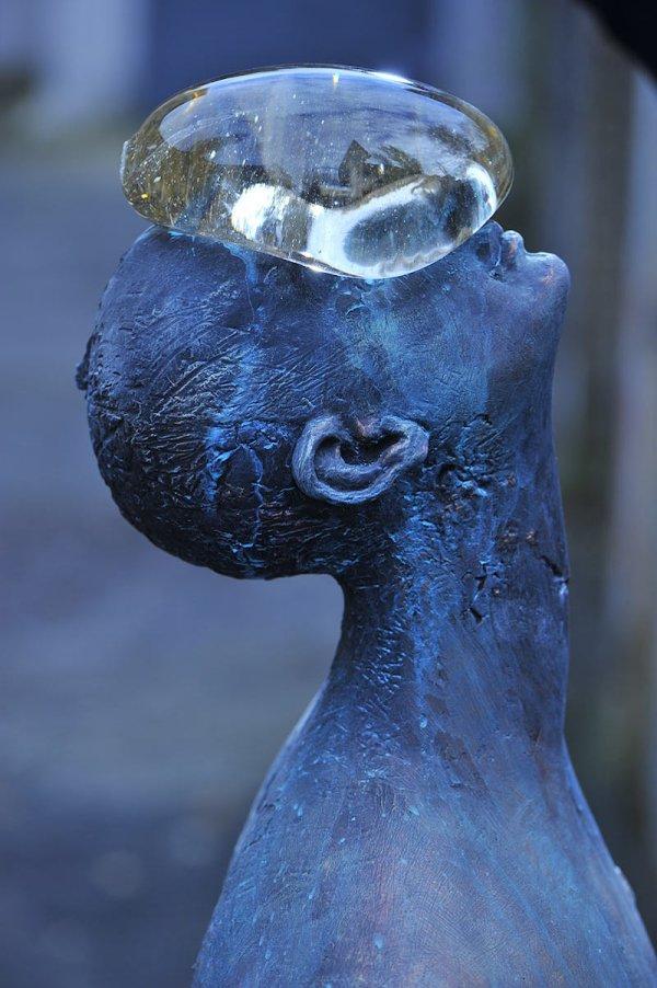 Giant Glass Raindrop Balances Bronze Man Face In