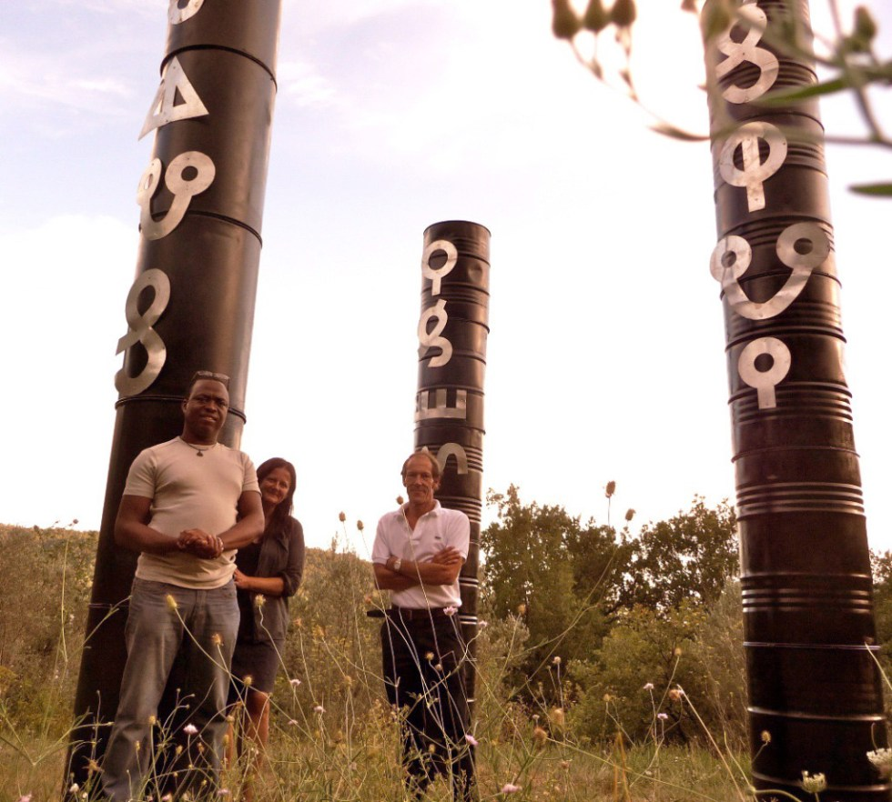 "An oil barrel sculpture installation with Afaka script which reads ""Save our Drinking Water"" by Marcel Pinas"