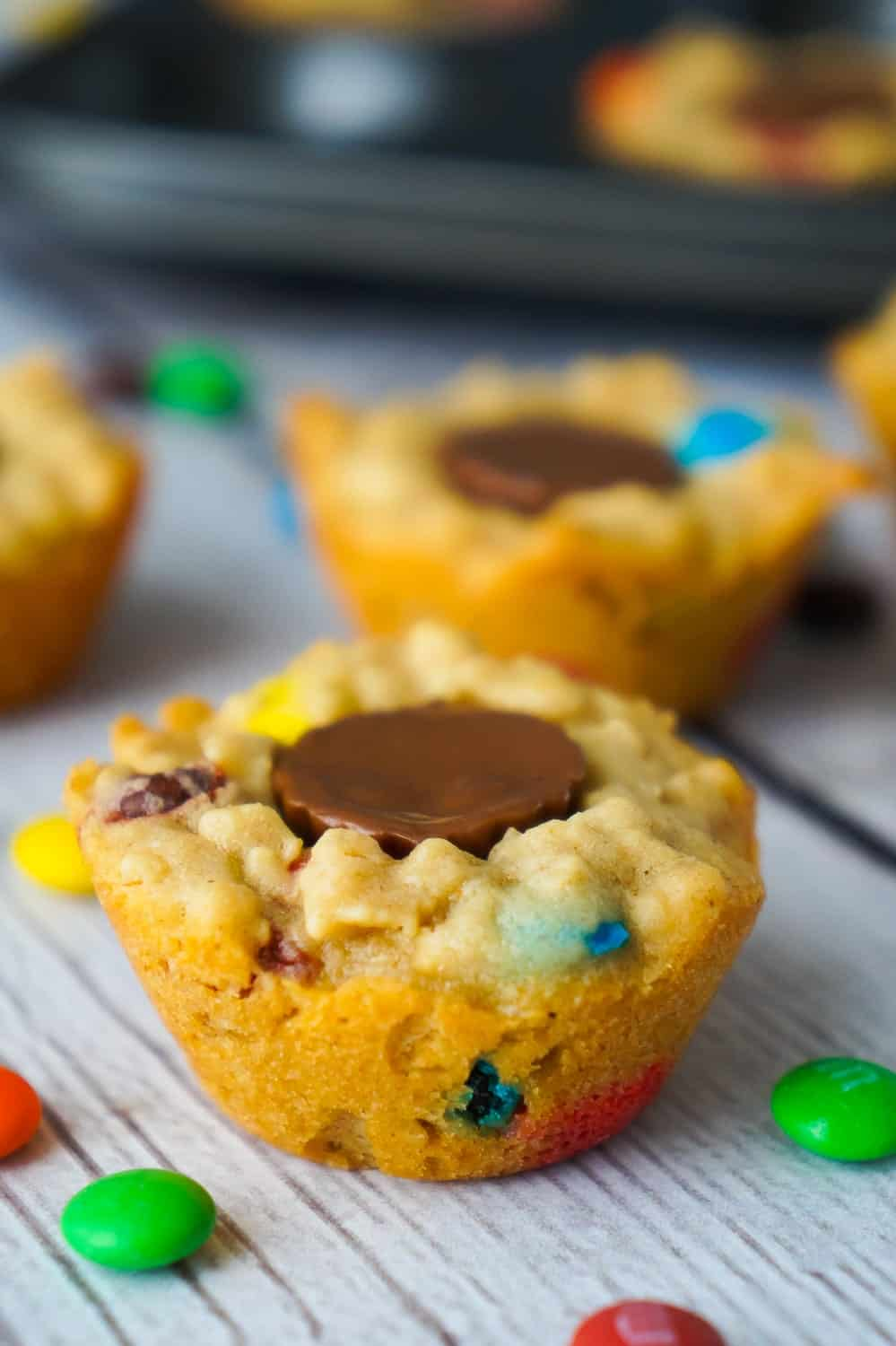 These Peanut Butter Cup Stuffed Monster Cookie Cups are a fun and easy dessert recipes. The oatmeal peanut butter cookies are loaded with mini M&Ms and each cookie cup has one mini Reese's peanut butter cup pressed into the center.