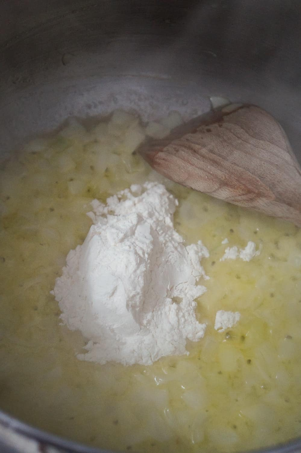 all purpose flour added to a pot with diced onions and butter