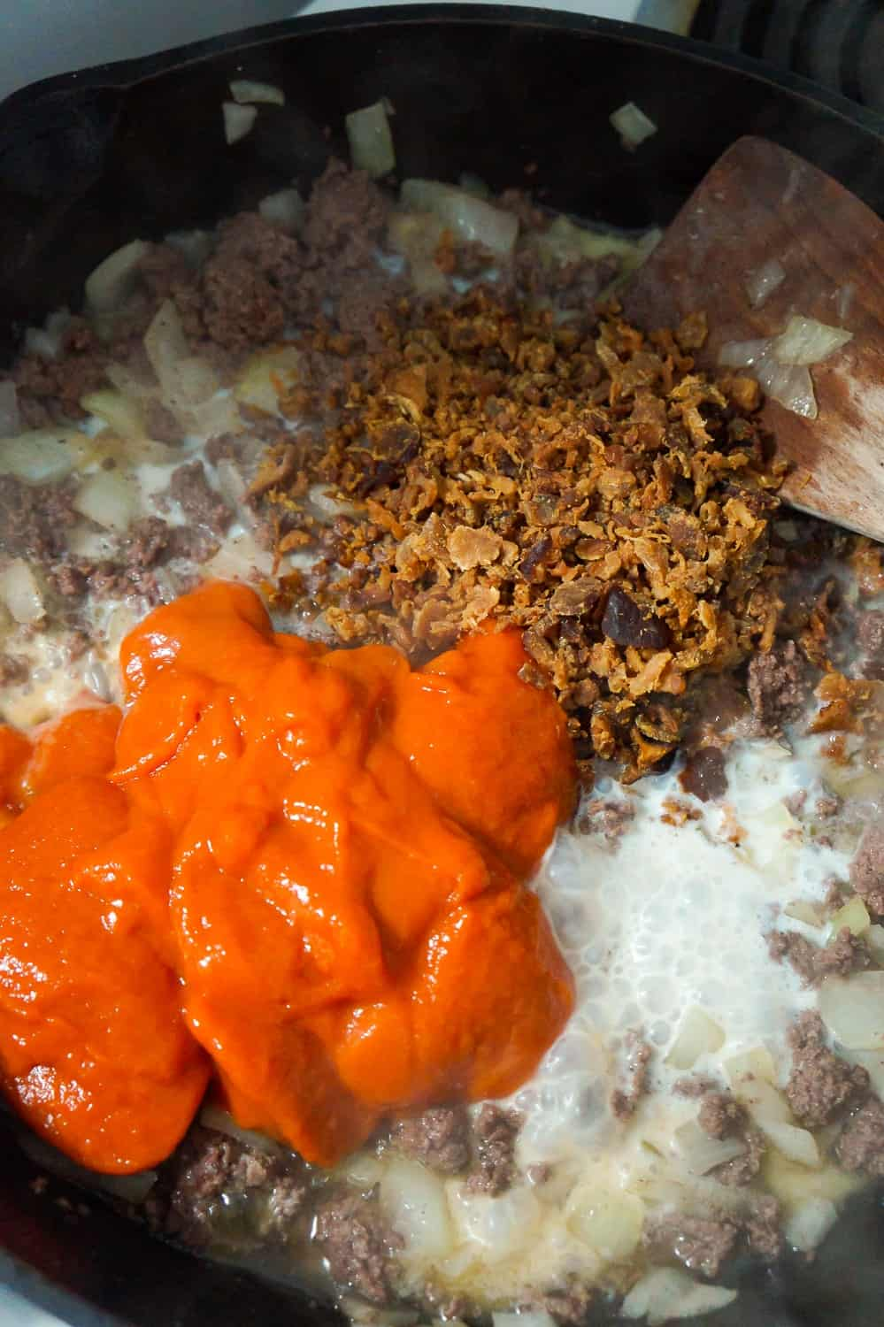 condensed tomato soup, milk and real bacon bits added to cooked ground beef in a frying pan