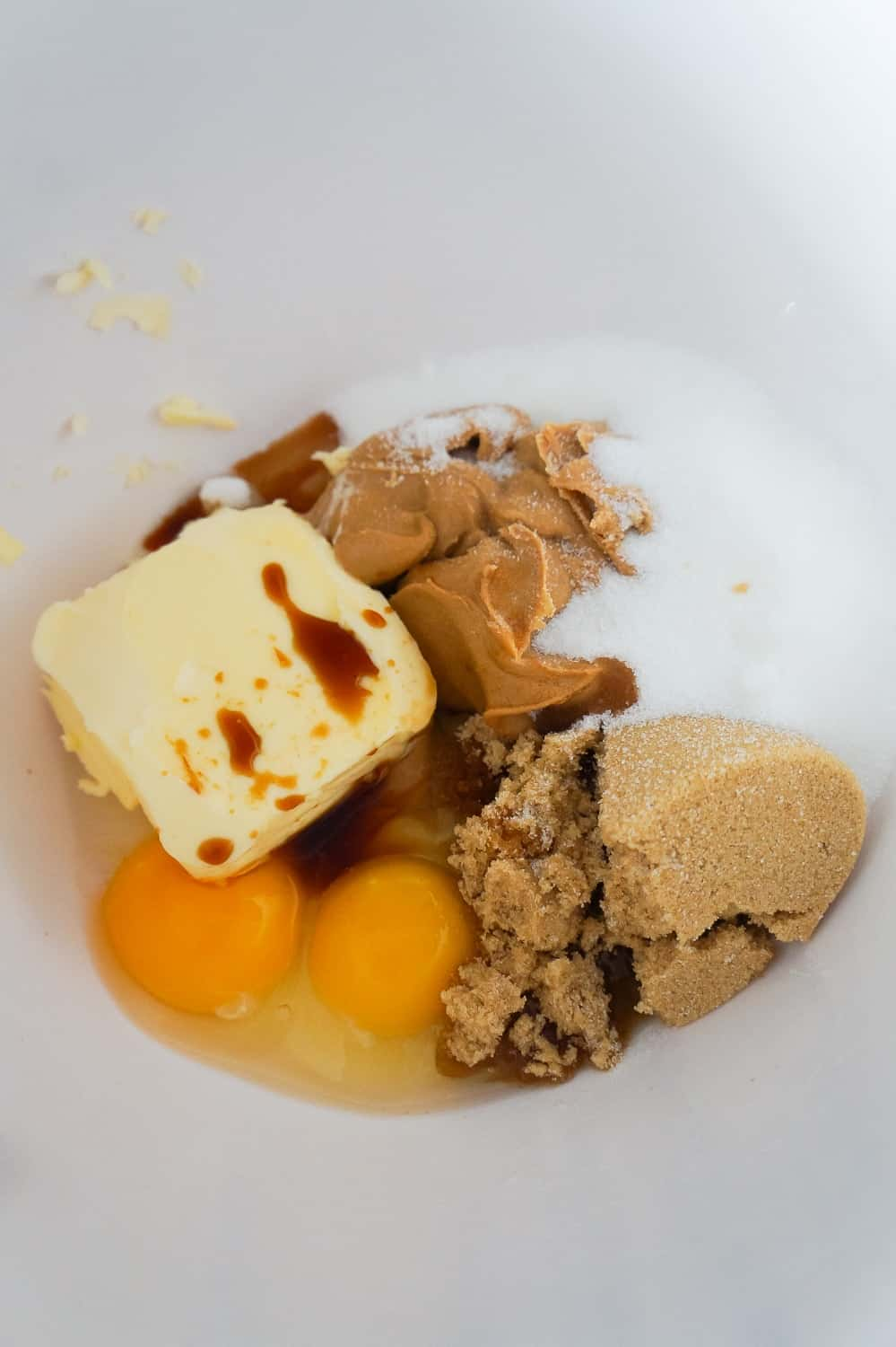 butter, peanut butter, eggs, brown sugar and white sugar in a mixing bowl