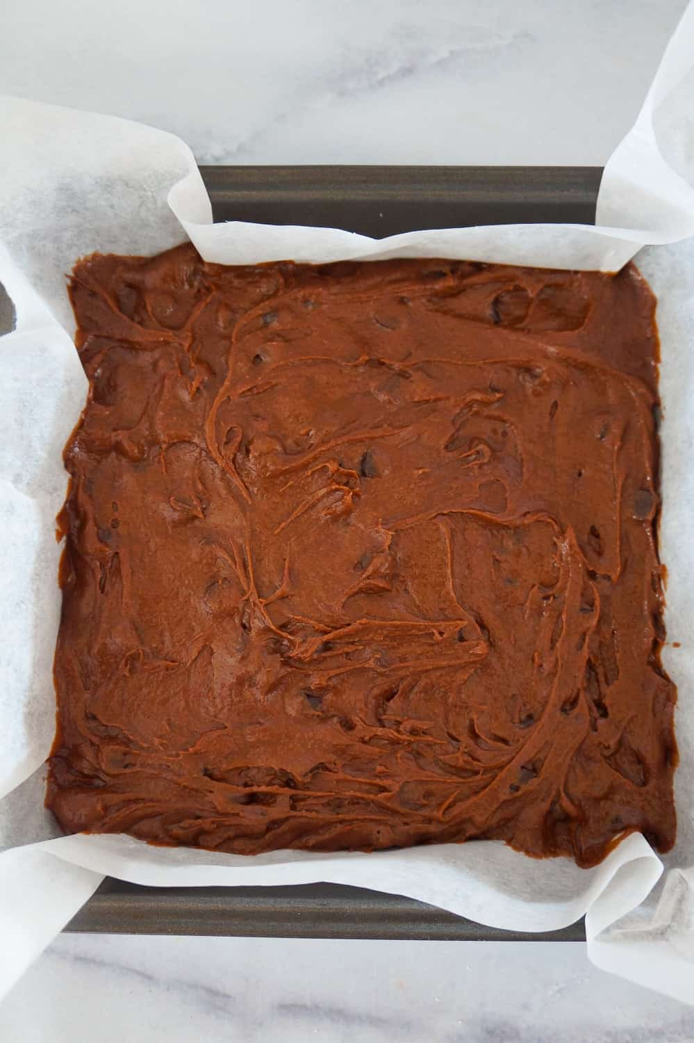 brownie batter in a parchment lined baking pan