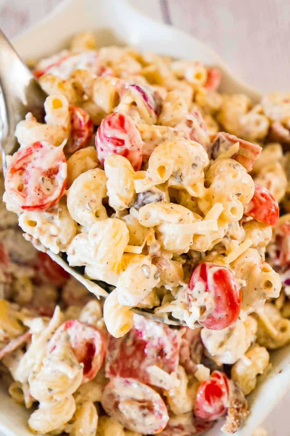 Italian Pasta Salad is a delicious cold side dish recipe perfect for potluck parties. This creamy pasta salad is loaded with cherry tomatoes, red onions, salami, bacon, basil pesto, Parmesan cheese and mozzarella cheese.