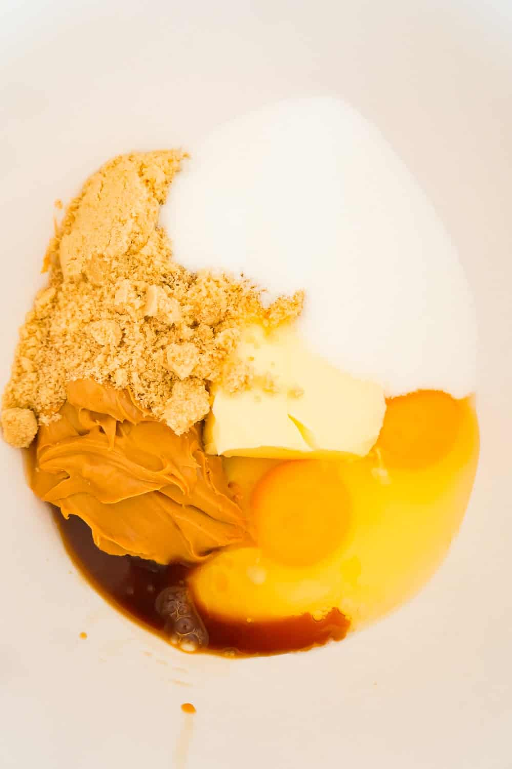 eggs, peanut butter sugar, brown sugar and vanilla extract in a mixing bowl