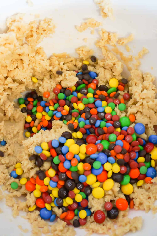 M&Ms and mini M&Ms on top of cookie dough in a mixing bowl