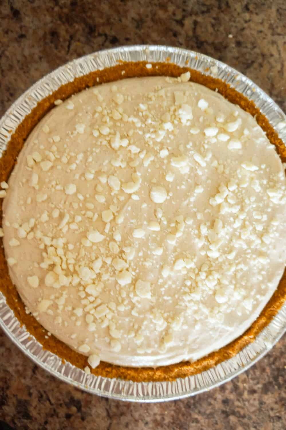 crumbled white chocolate on top of pumpkin spice cheesecake