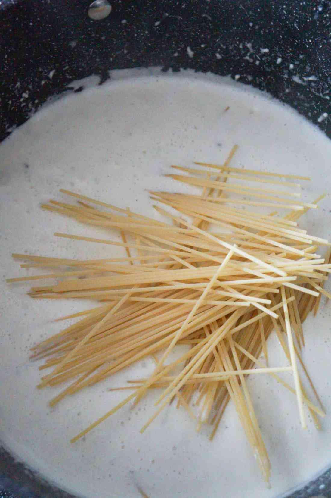 uncooked spaghetti in a pot with cream sauce