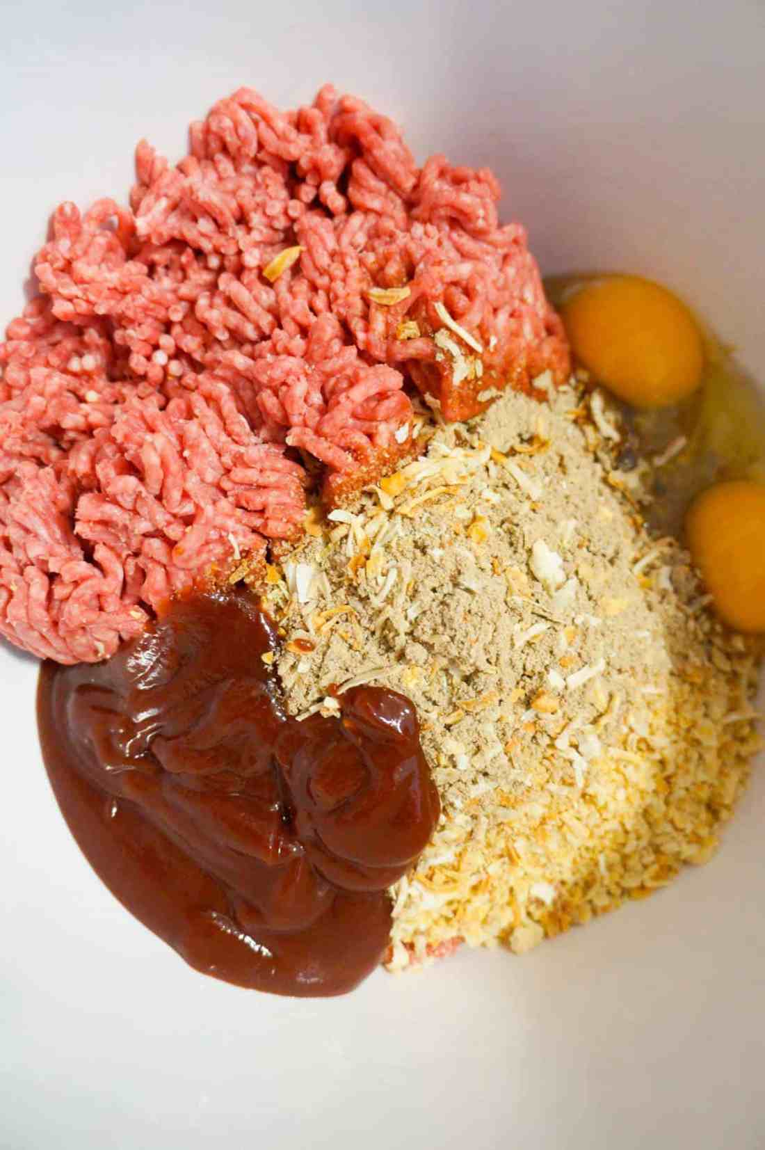 raw ground beef, Ritz cracker crumbs, bbq sauce and eggs in a mixing bowl