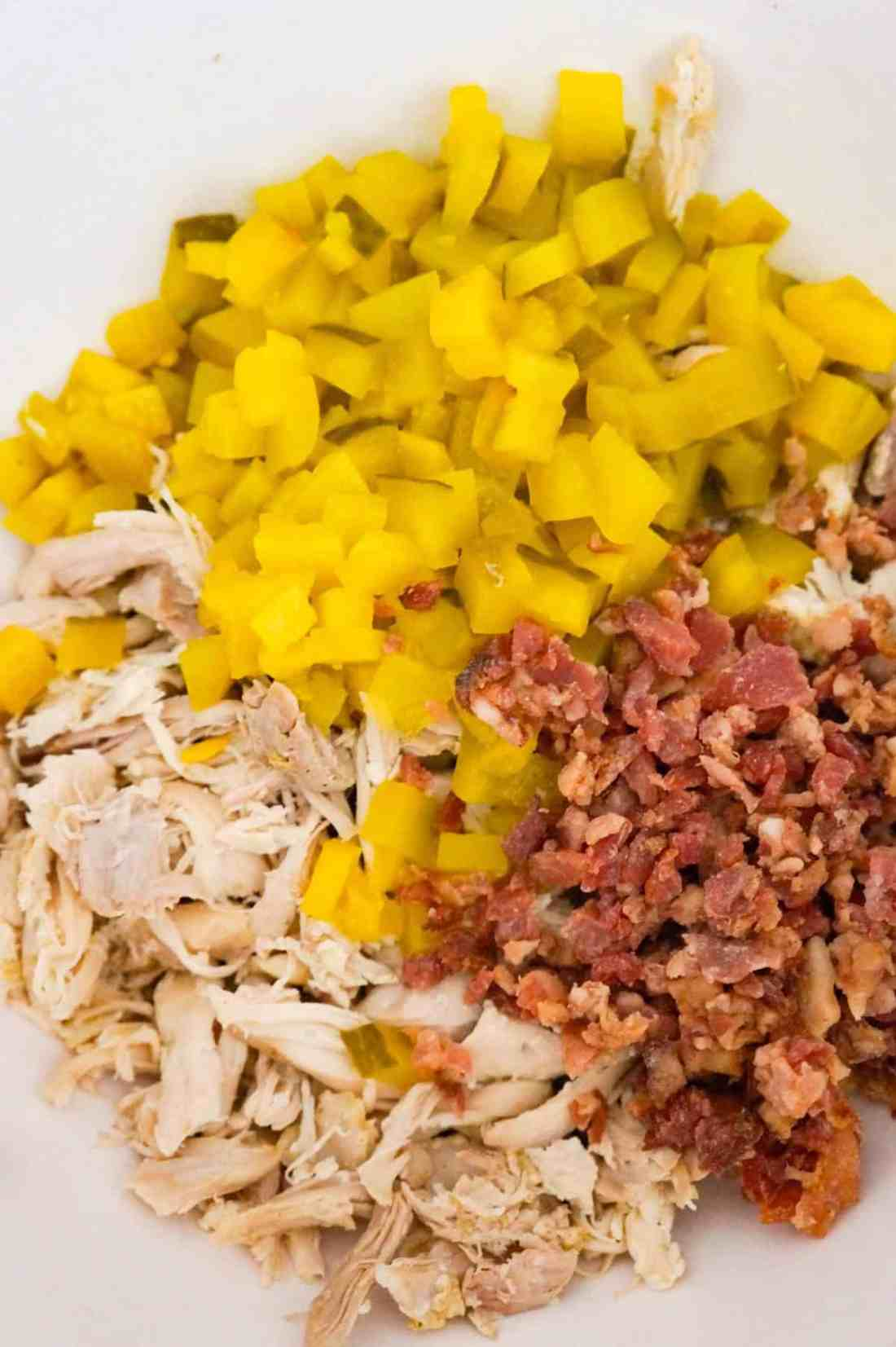 shredded chicken, diced dill pickles and crumbled bacon in a mixing bowl