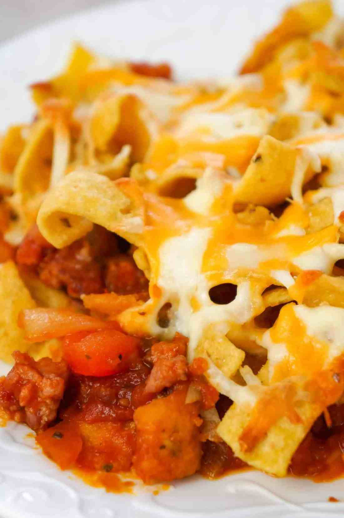 Sausage and Peppers Frito Pie is a delicious casserole recipe made with Italian pork sausage meat, onions and bell pepper tossed in a sweet and spicy tomato sauce and topped with Fritos corn chips and shredded cheese.