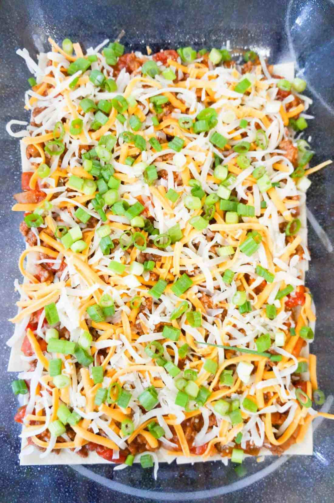 chopped green onions and shredded cheese on top of meat and tortillas in a baking dish