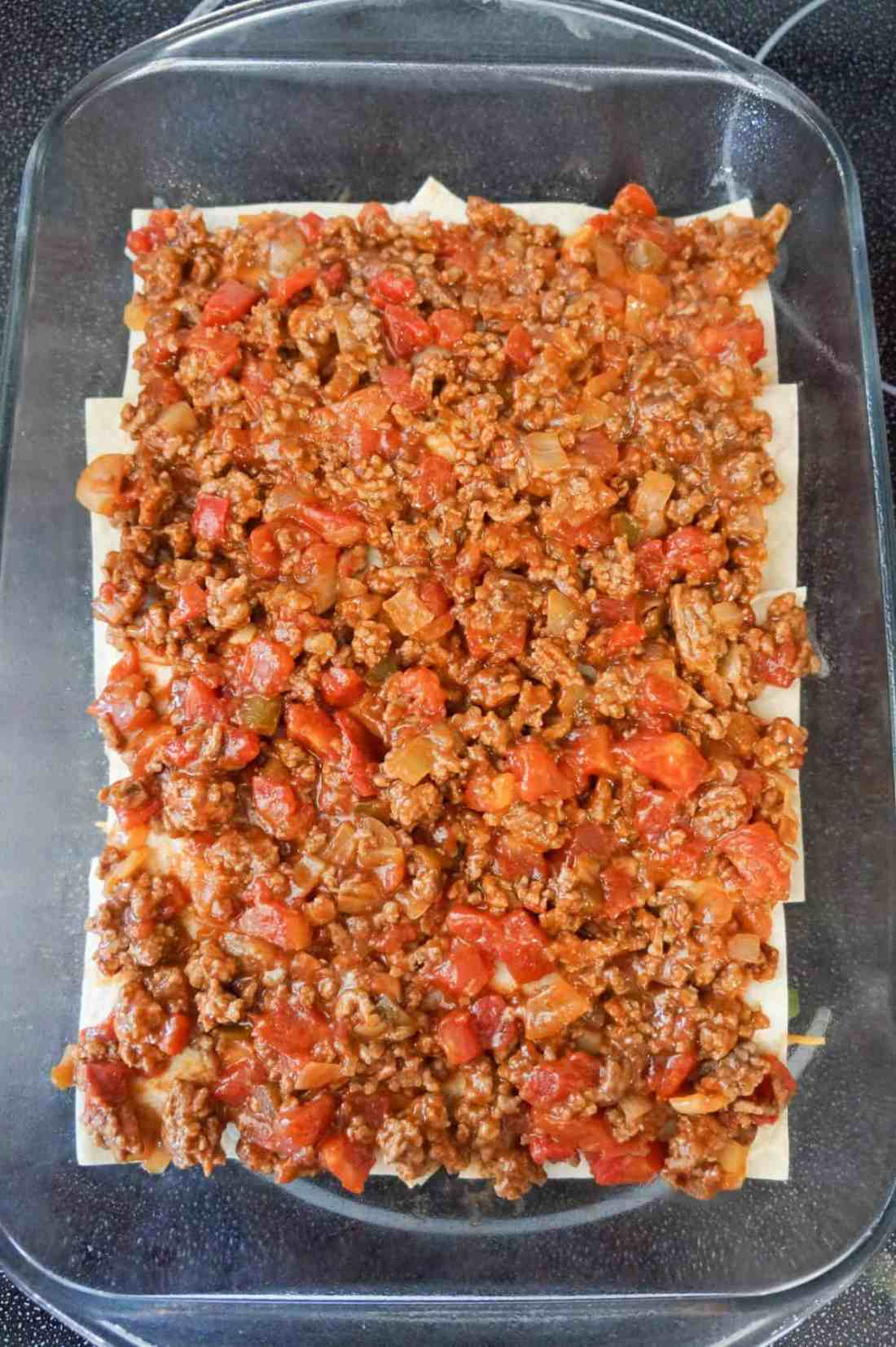 ground beef and salsa mixture on top of flour tortilla pieces in a baking dish