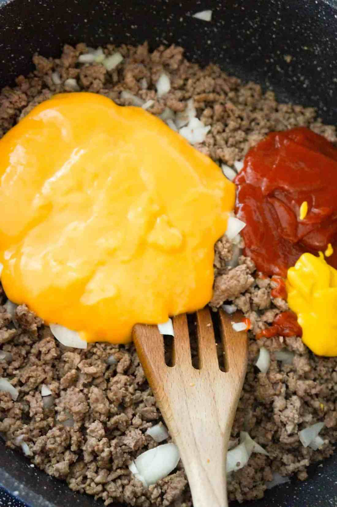 condensed cheddar cheese soup, ketchup and mustard on top of ground beef in a saute pan