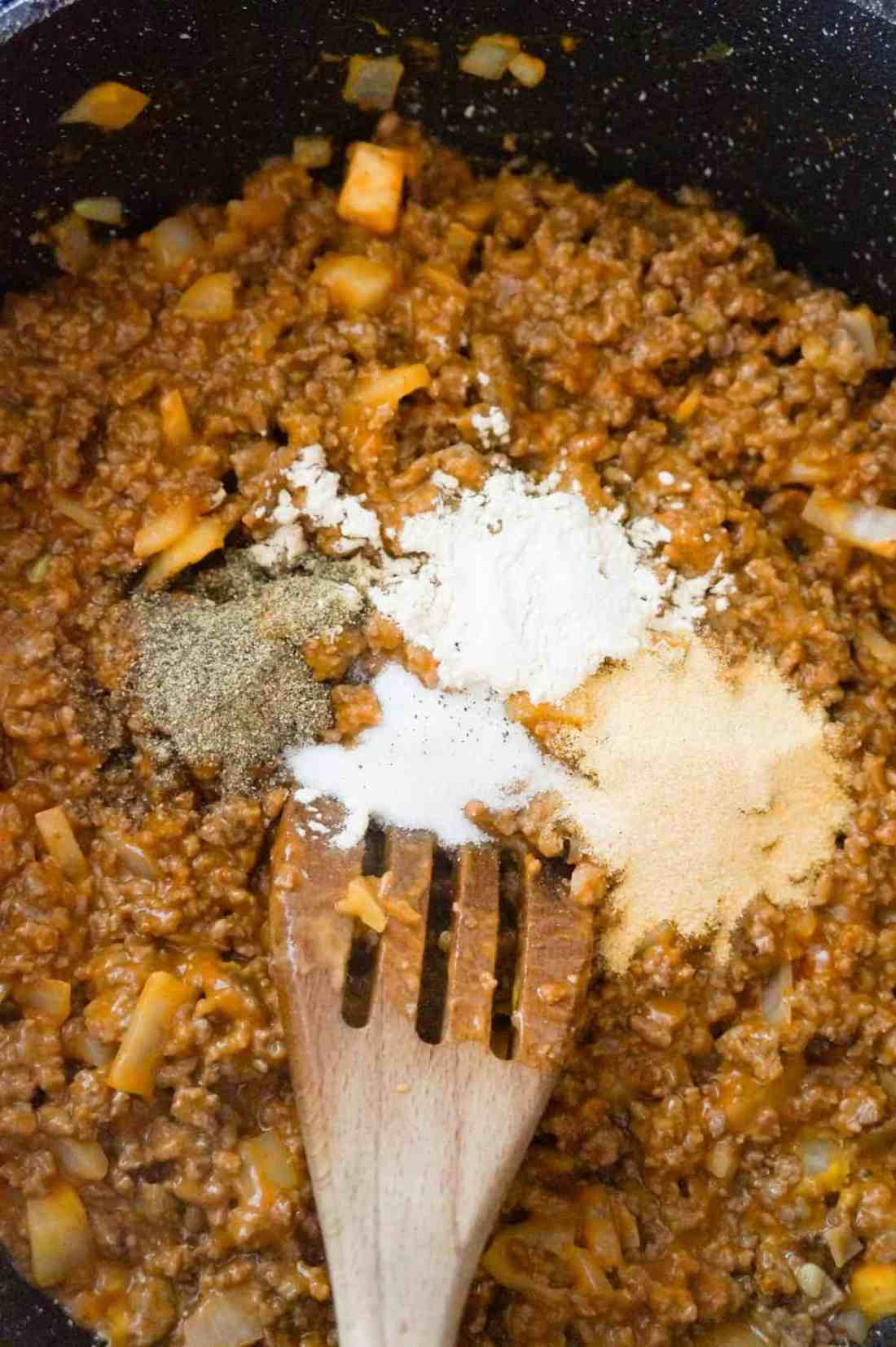 spices on top of ground beef mixture in a saute pan