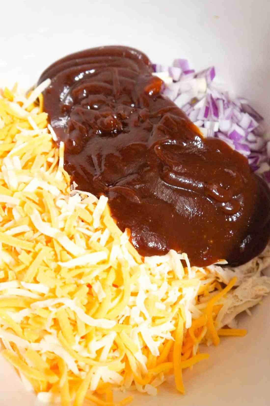 shredded cheese, bbq sauce and diced red onion on top of shredded chicken in a mixing bowl