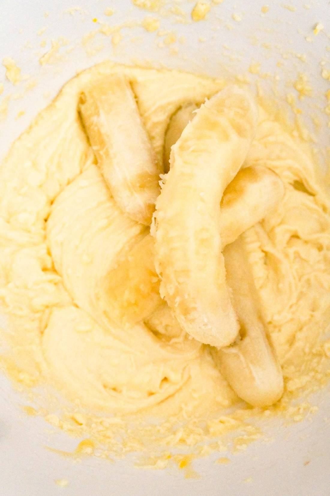 ripe bananas on top of creamy mixture in a mixing bolw