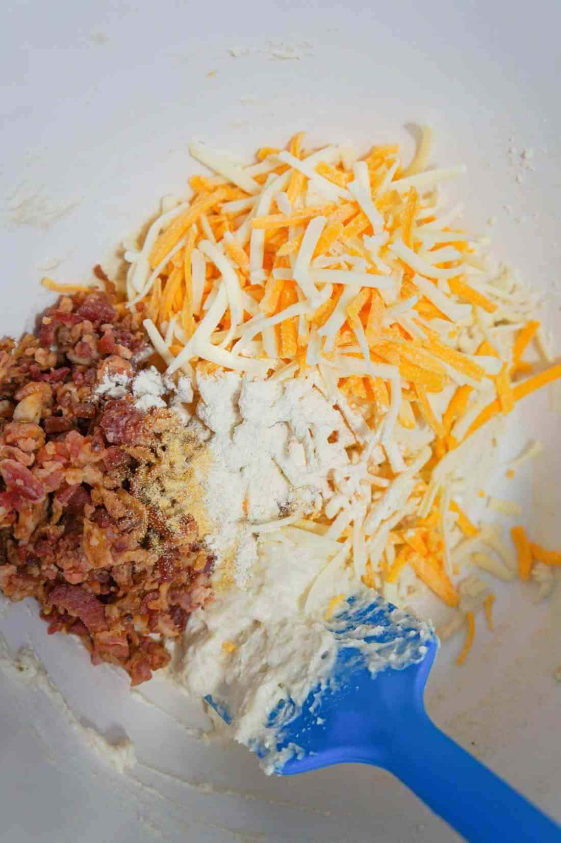 shredded cheese, crumbled bacon and spices on top of biscuit dough in a mixing bowl