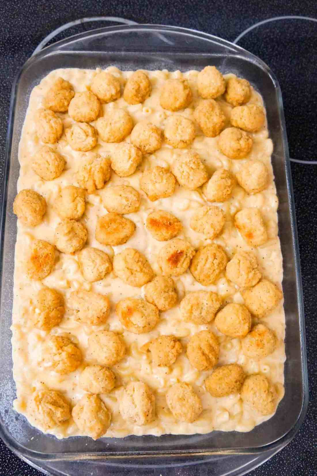 popcorn chicken on top of mac and cheese in a baking dish