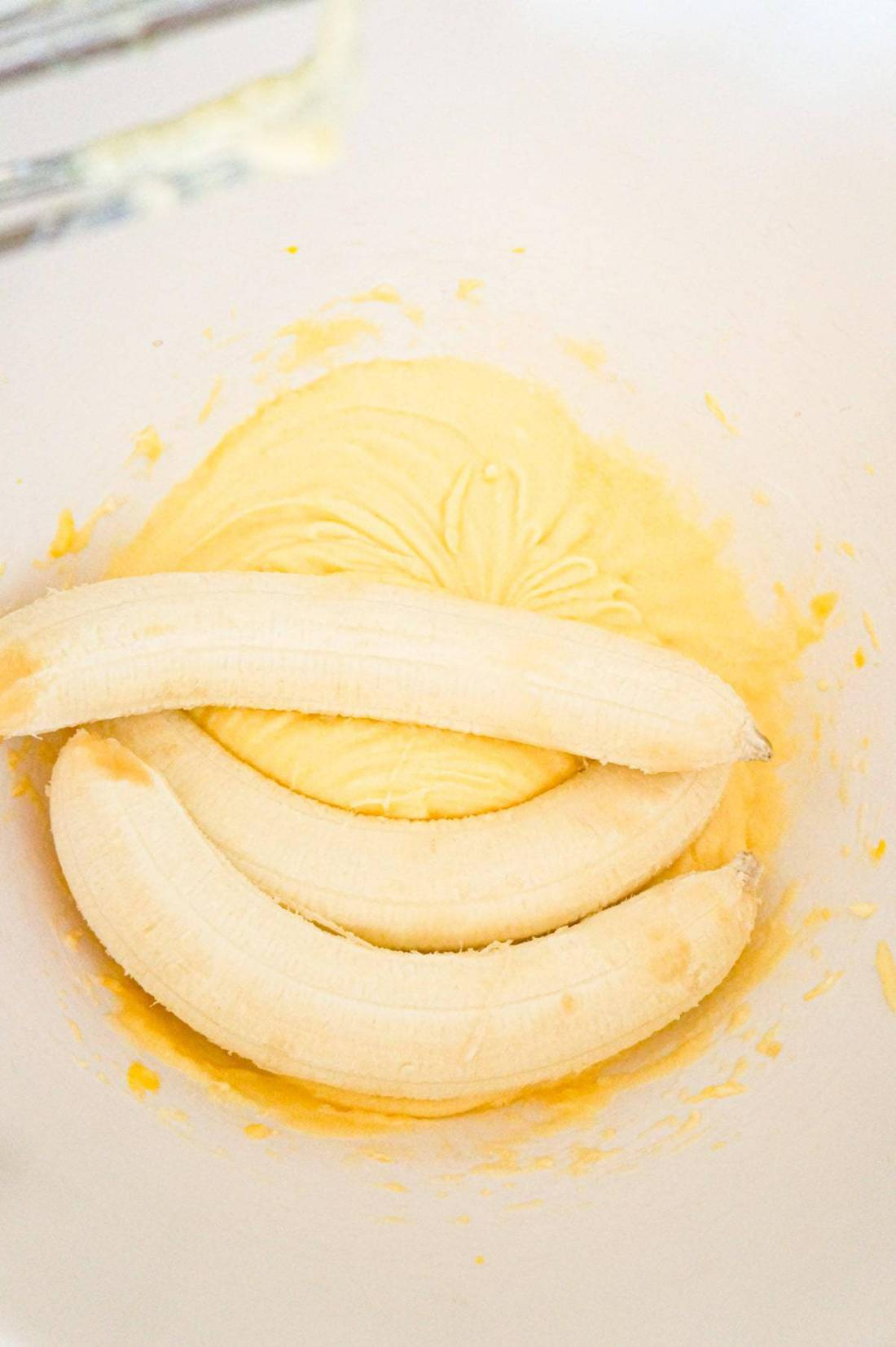 ripe bananas on top of creamed butter and sugar mixture in a mixing bowl