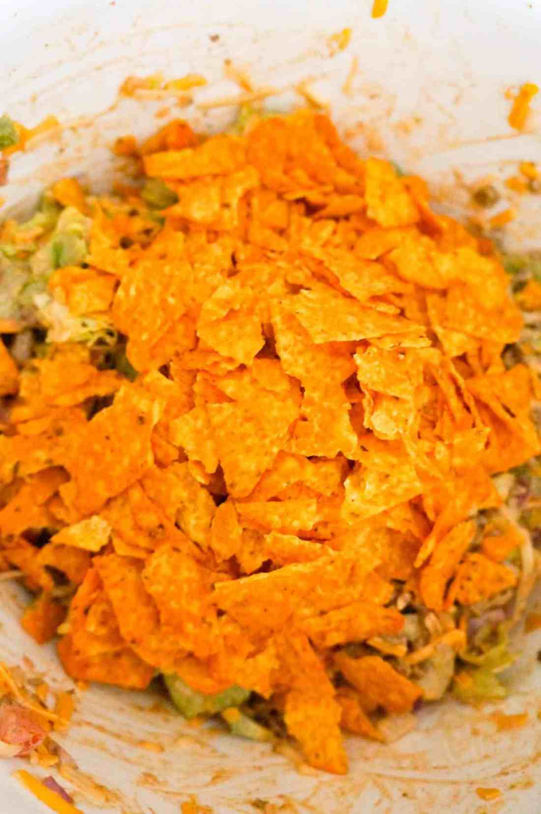 crumbled Doritos on top of salad in a mixing bowl