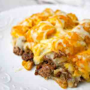 Shepherd's Pie Tater Tot Casserole is a hearty casserole with ground beef, corn and diced onions topped with mashed potatoes, tater tots and shredded cheese.