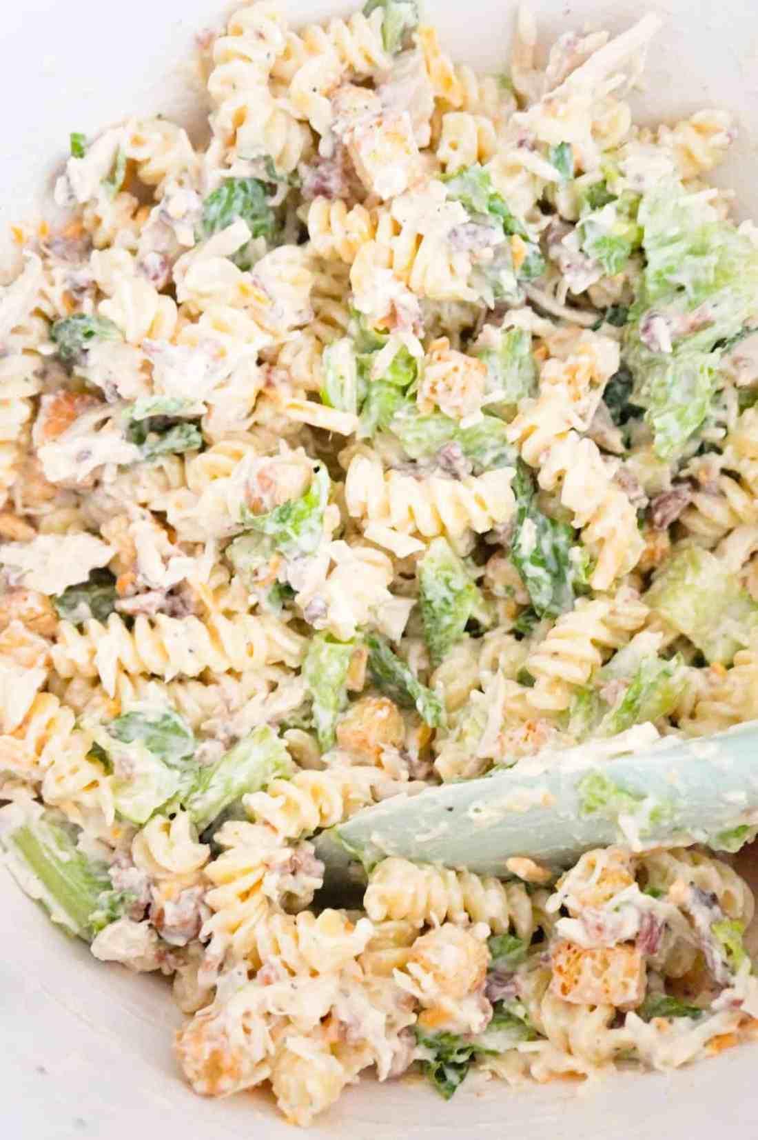 chicken caesar pasta salad in a mixing bowl