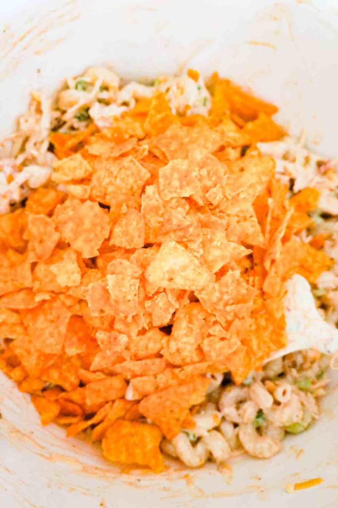 crumbled Doritos on top of pasta salad in a mixing bowl