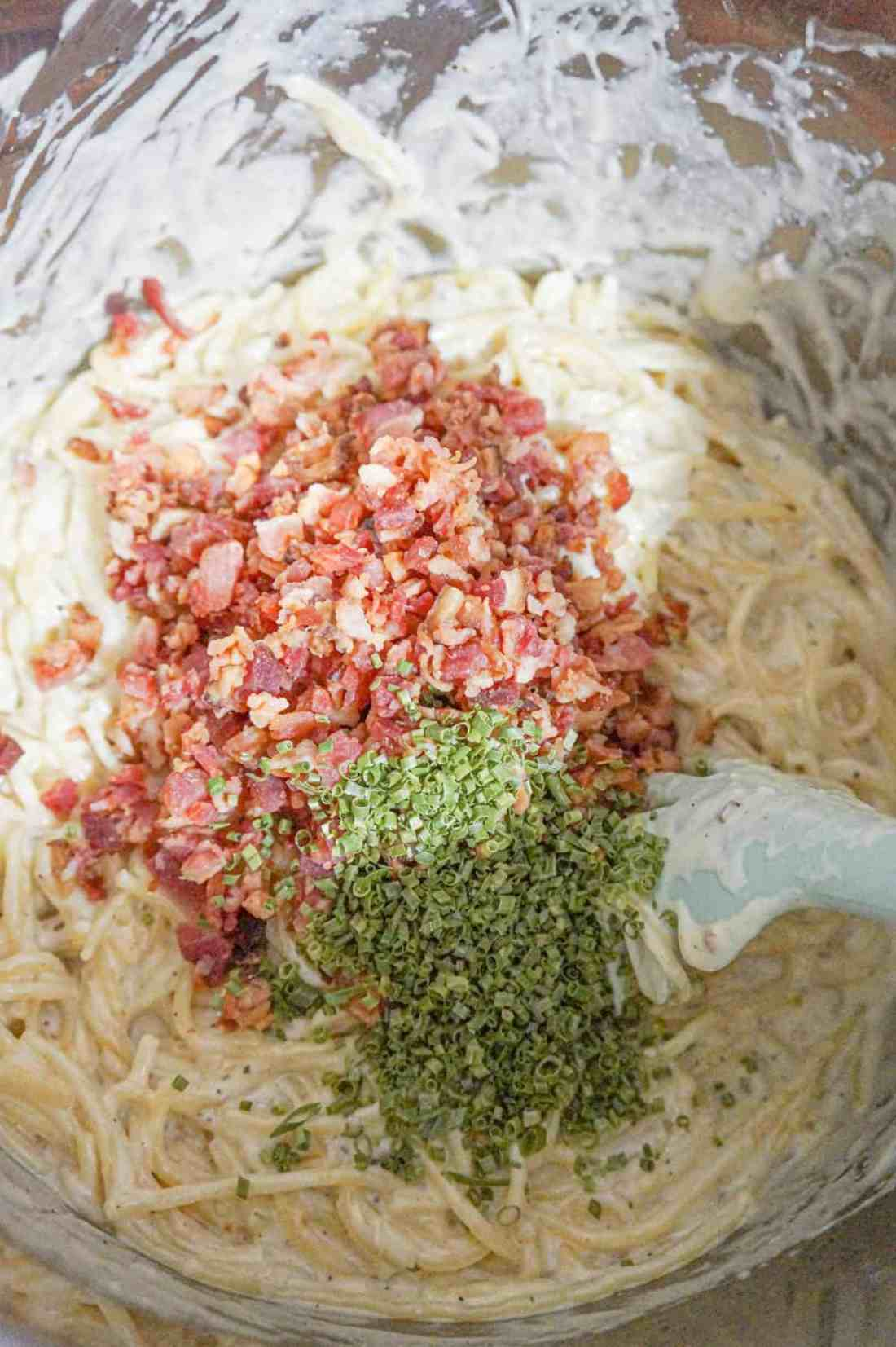 chopped chives and crumbled bacon on top of creamy spaghetti in an Instant Pot
