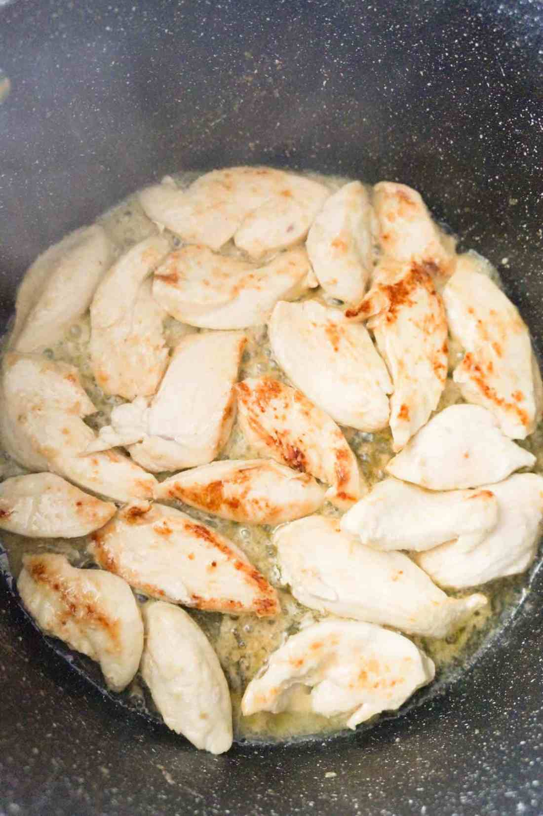 chicken breast slices cooking in butter in a large pot