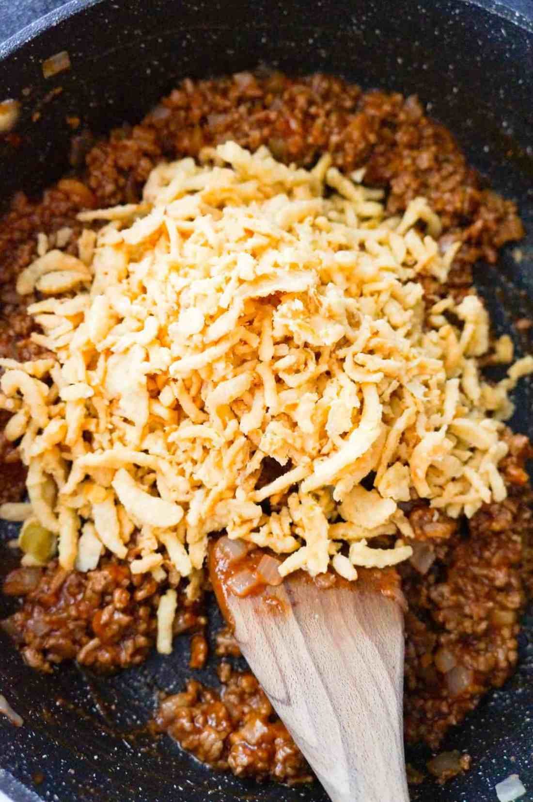 French's crispy fried onions on top of ground beef sloppy joe mixture in a saute pan