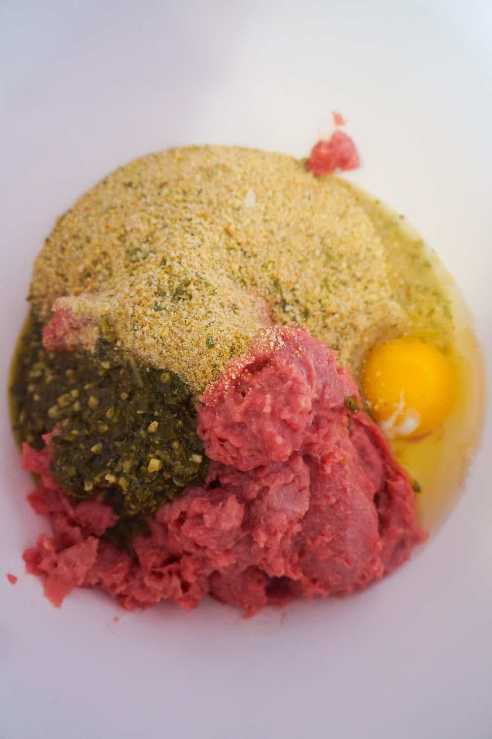 ground chicken in a bowl with bread crumbs, egg and basil pesto
